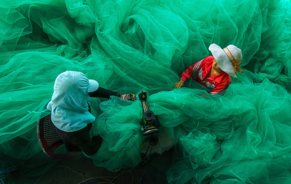 This vivid picture of two Vietnamese women sewing a fishing net, conveying the amazing things people can do with their hands: